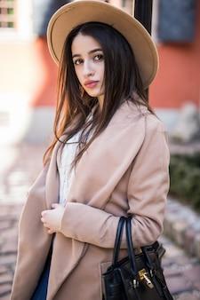 Belle femme brune aux cheveux longs marchant le long de la rue vêtue de vêtements d'automne décontractés
