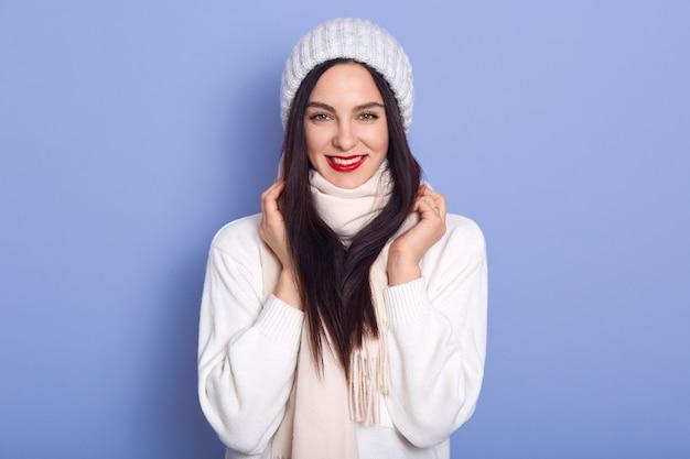 Belle femme brune aux cheveux longs portant une casquette chaude élégante et un pull blanc