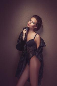 Belle femme brune aux cheveux longs sexy en lingerie noire et manteau de fourrure posant