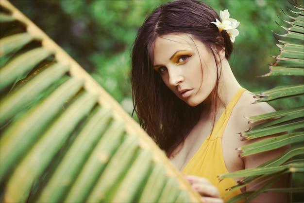 Belle femme brune aux cheveux mouillés dans une robe longue jaune entourée de plantes tropicales