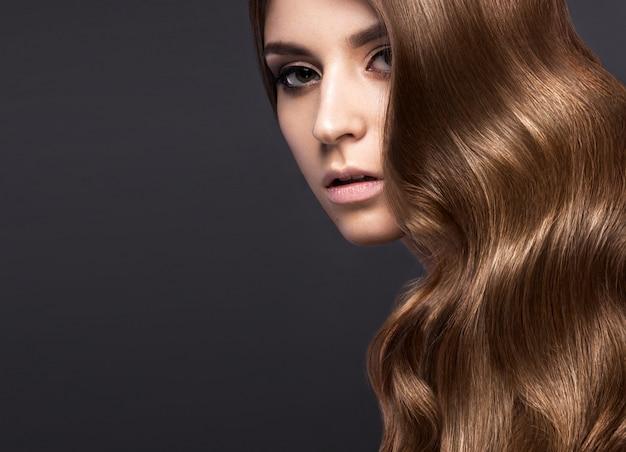 Belle femme brune aux cheveux parfaitement bouclés et maquillage classique