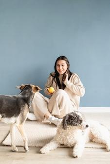 Belle femme brune avec chien de race mixte ludique