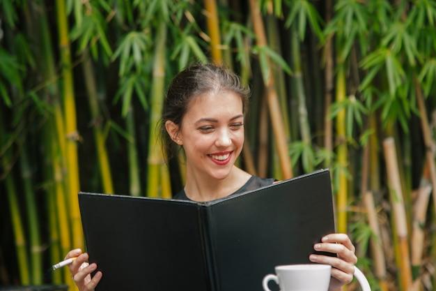 Belle femme brune, choisir la nourriture dans un menu de restaurant