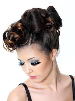 Belle femme brune avec une coiffure de mode moderne sur blanc