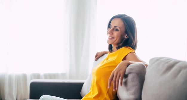Belle femme brune confiante calme se repose sur le canapé à la maison pendant les vacances