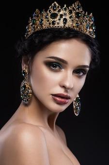 Belle femme brune avec une couronne d'or, des boucles d'oreilles et du maquillage de soirée professionnel