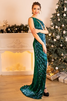 Belle femme brune dans une robe verte se dresse dans le contexte d'un arbre de noël et d'une cheminée, des bougies brûlent autour.