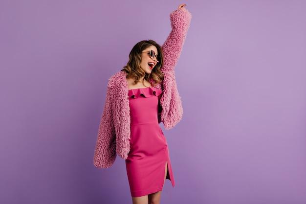 Belle femme brune dansant sur un mur violet
