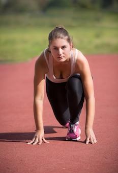 Belle femme brune debout sur la ligne de départ et prête à courir