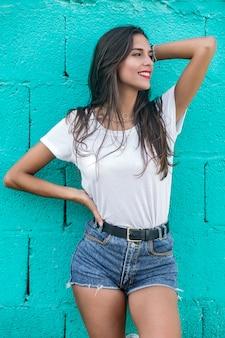 Belle femme brune debout près d'un mur turquoise