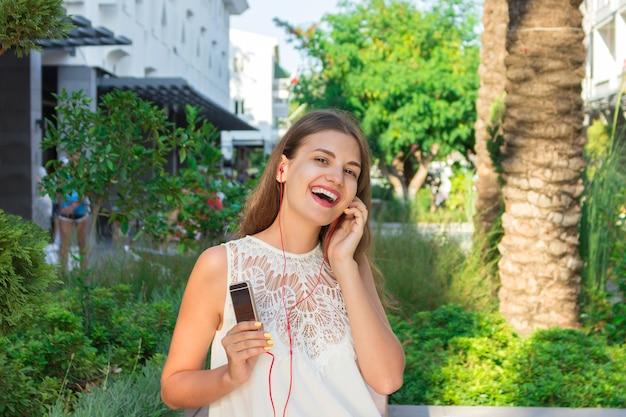 Belle femme brune écoute de la musique dans des écouteurs dans le parc. elle porte une robe blanche à la mode.