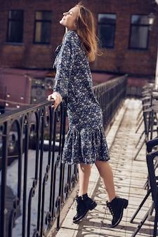 Belle femme brune élégante portant une robe d'été bleue sur le balcon