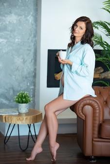 Belle femme brune enceinte dans une chemise est assise sur un canapé dans un salon