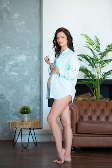 Belle femme brune enceinte dans une chemise est assise sur un canapé est titulaire d'une tasse et boit du thé