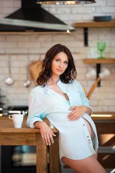 Belle femme brune enceinte dans une chemise est assise dans la cuisine avec une tasse de thé.
