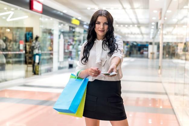 Belle femme brune avec fan de dollar dans le centre commercial