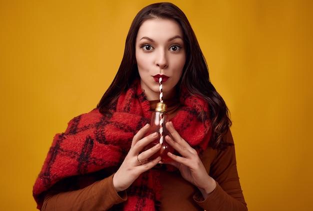Belle femme brune avec une grande écharpe tricotée rouge buvant un thé chaud
