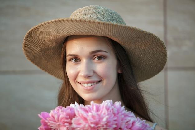 Belle femme brune heureuse au chapeau, sentant un bouquet de fleurs