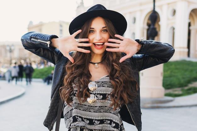 Belle femme brune incroyable avec une longue coiffure ondulée au printemps ou à l'automne tenue urbaine élégante marchant dans la rue. lèvres rouges, corps mince. concept de mode de rue.