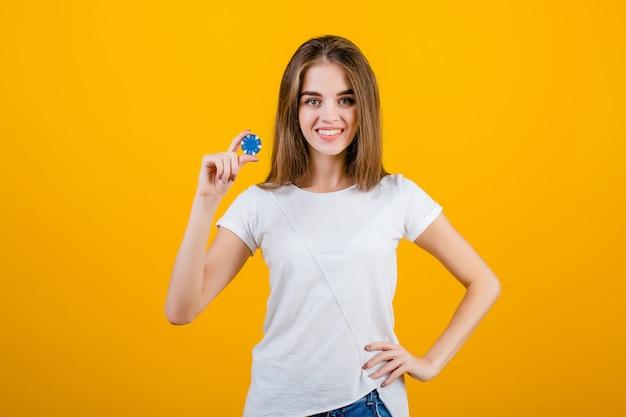 Belle femme brune avec jeton de poker bleu du casino en ligne isolé sur jaune