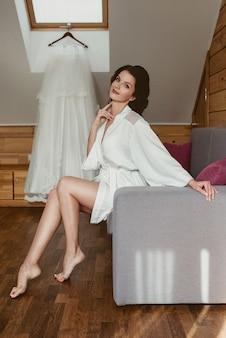 Belle femme brune joyeuse mariée en robe de soie blanche se préparant au mariage