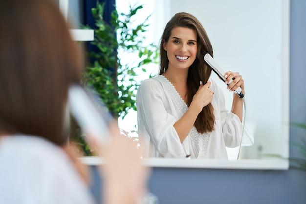 Belle femme brune lissant les cheveux dans la salle de bain