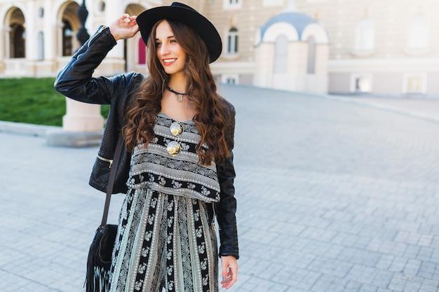 Belle femme brune avec une longue coiffure ondulée au printemps ou à l'automne tenue urbaine élégante marchant dans la rue. lèvres rouges, corps mince. concept de mode de rue.