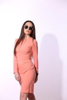 Belle femme brune avec des lunettes de soleil et des cheveux longs posant