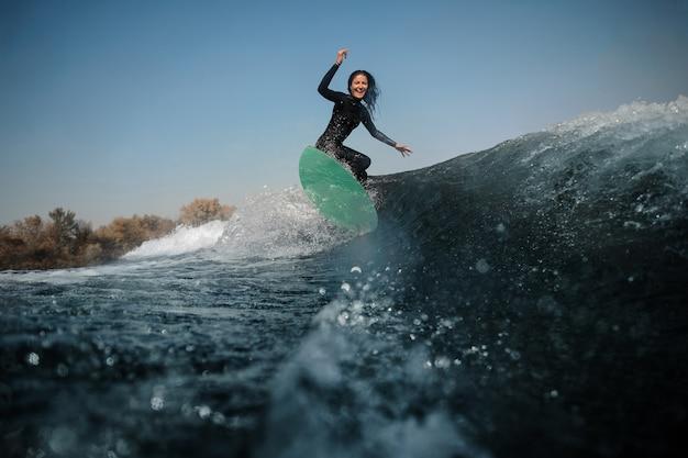 Belle femme brune en maillot de bain blanc à cheval sur le wakeboard vert sur les genoux pliés