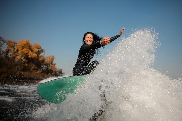 Belle femme brune en maillot de bain blanc sautant sur le wakeboard vert sur les genoux pliés