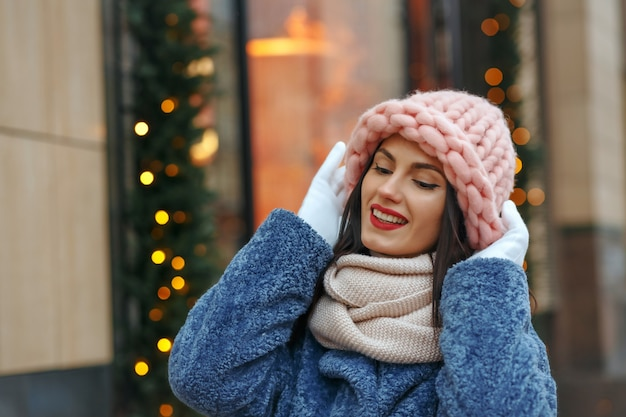 Belle femme brune en manteau marchant dans la ville en hiver. espace libre