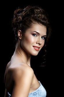 Belle femme brune avec maquillage et coiffure de soirée