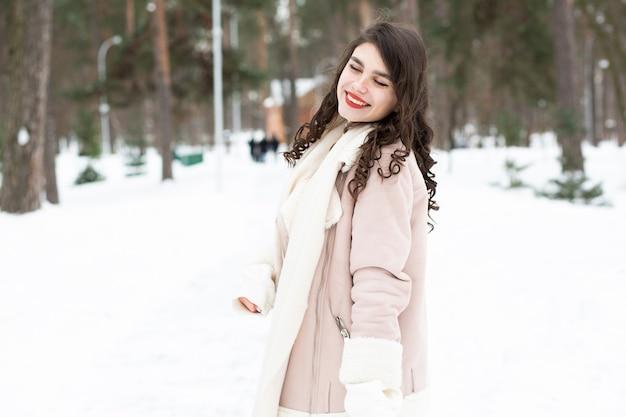 Belle femme brune marchant dans la forêt en hiver. espace pour le texte