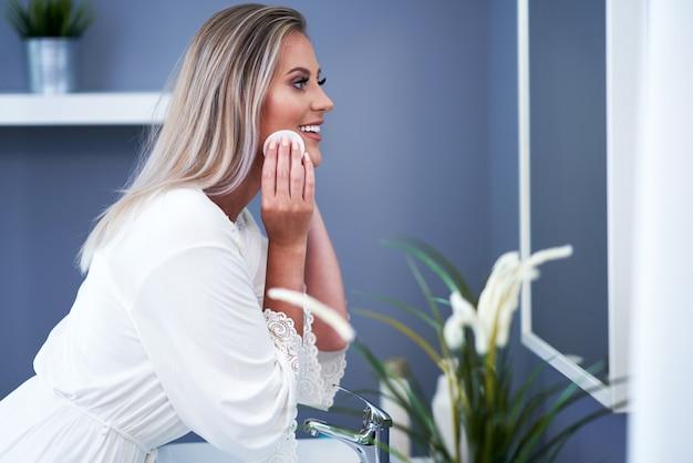 Belle femme brune nettoyant le visage dans la salle de bain