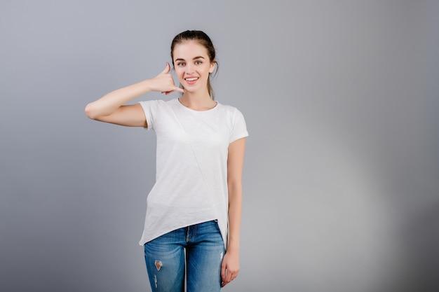 Belle femme brune portant une chemise blanche montrant appelez-moi geste geste imitant téléphone avec main isolé sur gris