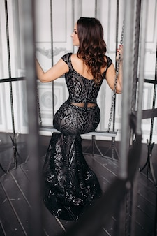 Belle femme brune portant une robe noire brillante posant en cage comme oiseau