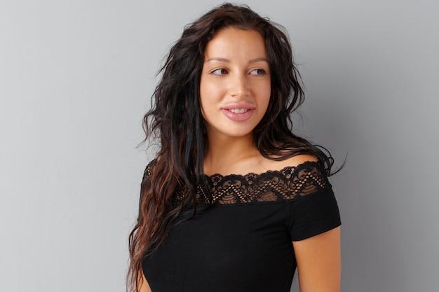 Belle femme brune posant sur un fond gris