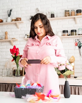 Belle femme brune prenant la photo d'oeufs de pâques décorés à l'aide de téléphone portable dans la cuisine