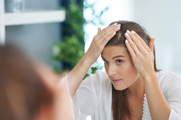 Belle femme brune avec des problèmes de peau dans la salle de bain