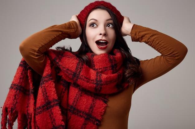 Belle femme brune en pull et bonnet rouge avec une grande écharpe tricotée