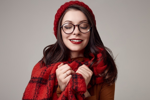 Belle femme brune en pull, lunettes et bonnet rouge avec une grande écharpe tricotée