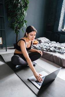 Belle femme brune de remise en forme faire des exercices d'étirement devant un ordinateur portable, faire du yoga à l'intérieur à la maison