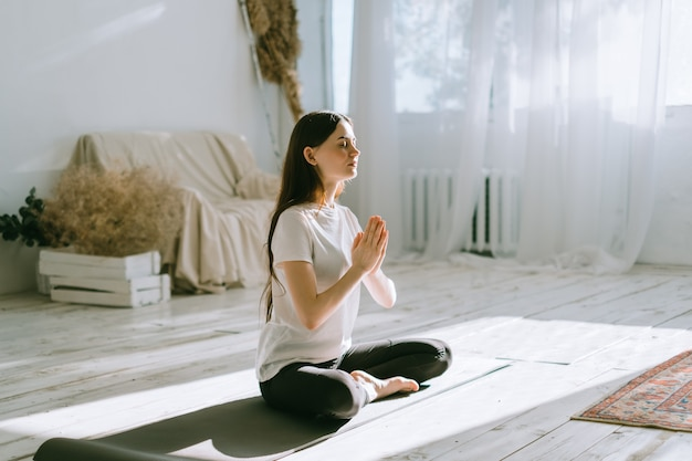 Belle femme brune de remise en forme méditer, faire du yoga à l'intérieur à la maison