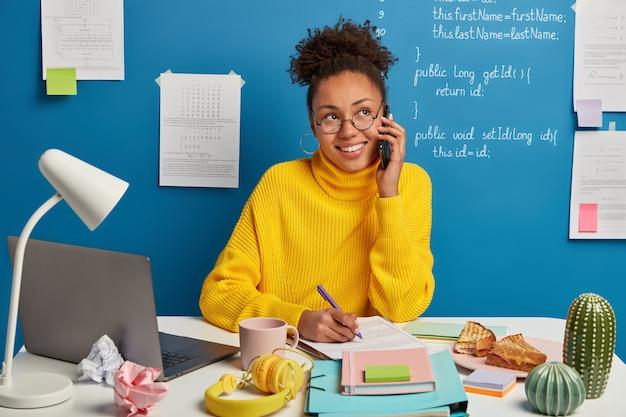 Belle femme brune restant sur son lieu de travail
