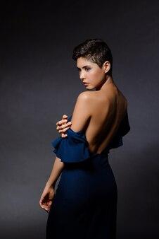 Belle femme brune en robe de soirée posant