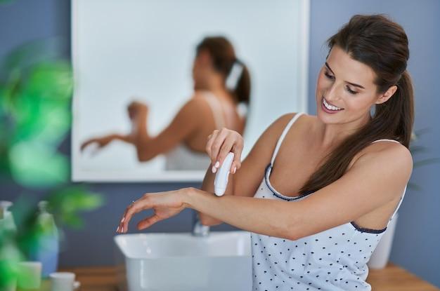 Belle femme brune s'épilant les bras dans la salle de bain