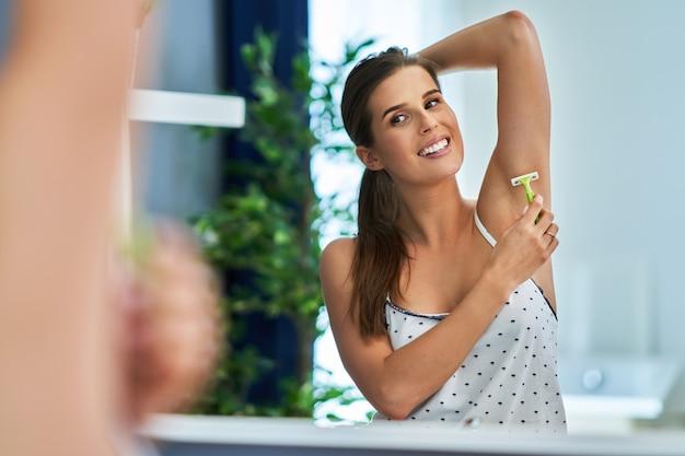 Belle femme brune se rasant les aisselles dans la salle de bain