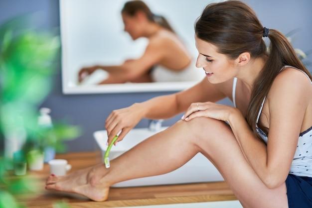 Belle femme brune se rasant les jambes dans la salle de bain