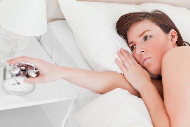 Belle femme brune se réveiller avec une horloge en position couchée