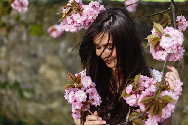 Belle femme brune sent les fleurs roses sur la floraison de l'arbre sakura